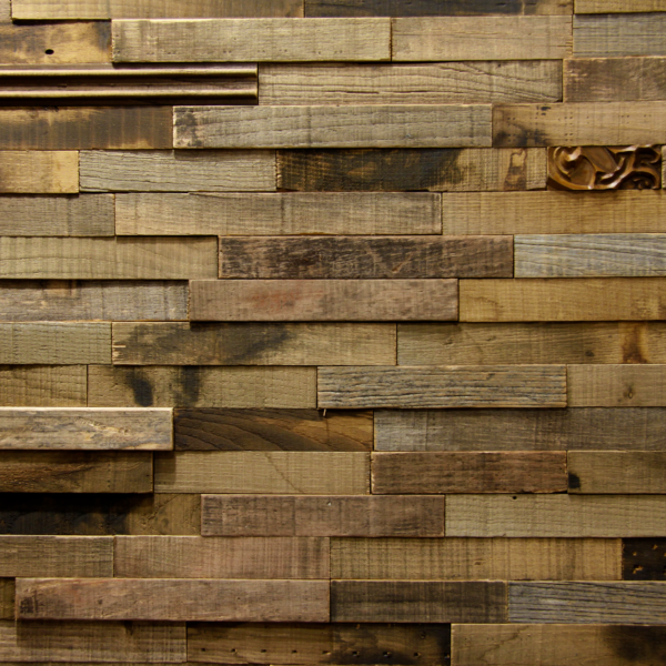 An accent wall made from natural raw wood, mixing simple strips with CNC machined ones.