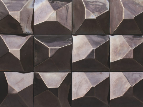 A tile that reminds a bevel, which is a detail that stand-out from the rest of the piece. In this case, the tile looks like a half-cut pyramid.