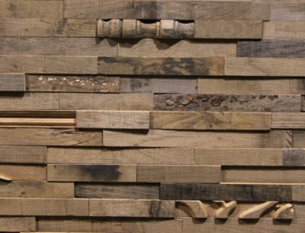 A wood panel, made from small rectangular wood strips. These wood strips are organized on a horizontal layout, and sometimes a piece with unusual patterns that resemble antique wood details shows. The tonality of the wood is light-to-medium brown.