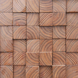 A wood design with a lot of cubes. Each cube has a different height and is oriented differently. The wood cuts are very noticeable on the front of each cube, creating a small mesmerizing pattern.